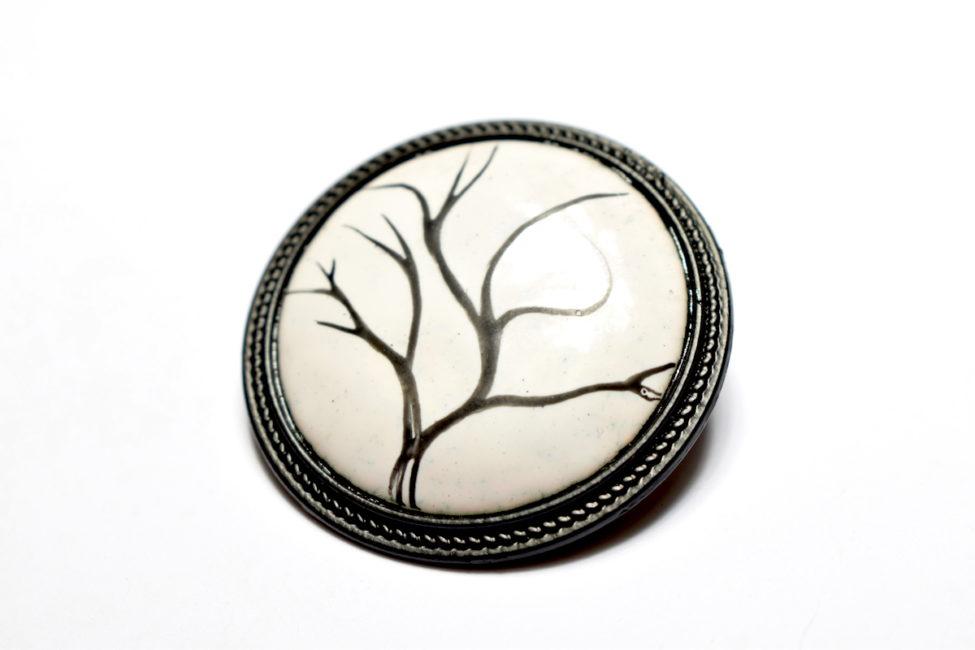 Broche ronde sertie en émail peint au motif d'arbre